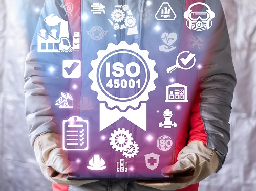 Worker wearing PPE holding a tablet that shows a graphic representation of ISO 45001 including safety icons.