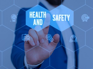"""Business person pointing finger to a graphic that says """"Health and Safety""""."""
