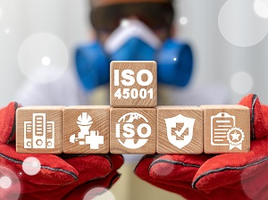A worker in full PPE holding up building blocks that say ISO 45001 and have various safety graphics on them.