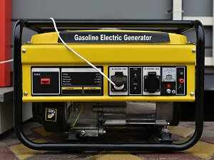 Portable generator that is yellow and black and says Gasoline Electric Generator on the side of it.