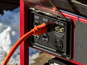 Close-up view of an extension cord plugged into a generator.