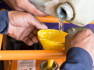 Two people pouring fuel into a generator safely.