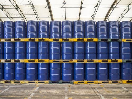 Blue industrial drums stacked neatly on pallets three tiers high.