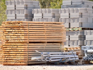 Lumber and masonry blocks stacked alongside other construction materials near an outdoor construction site.
