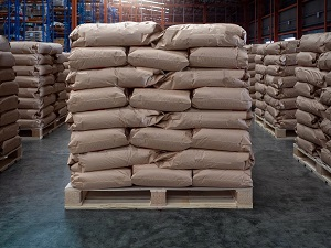 Bags are stacked in an interlocking formation on top of a pallet inside a warehouse.