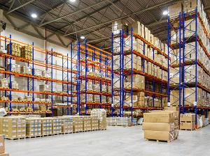 Boxes and materials stacked on steel racking inside a large warehouse.