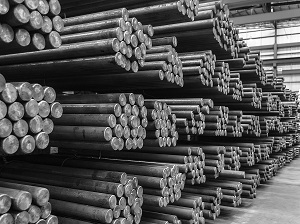 Steel rods stacked carefully on metal racks inside a warehouse.