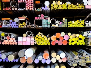 Metal rods that are color coded on the ends stacked neatly in racks to create a colorful display.
