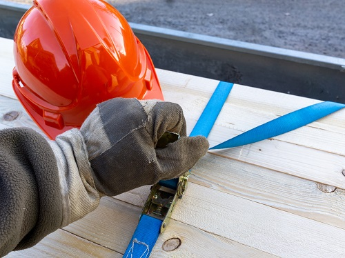 Worker wearing a glove is tightening a strap that is securing lumber on a trailer and a red hardhat is nearby.