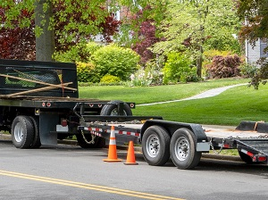 Large trailer that is pulled behind a truck being used for a landscaping company.