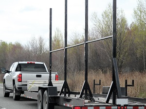 White pick-up truck towing a trailer loaded with materials.