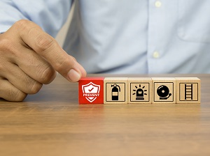 Person's hands touching some small wooden blocks with fire safety logos on them.