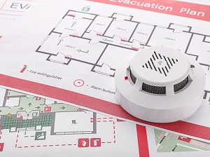 A smoke detector sitting on top of printed evacuation building plans as an image that depicts fire safety awareness.