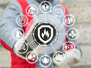 A worker wearing safety gear in the background touching a graphic with fire safety logos.