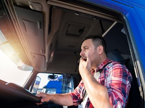 Tired truck driver who is yawning.