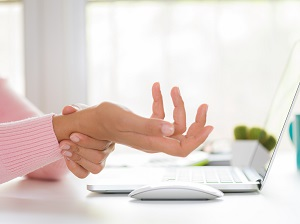 Office worker experiencing carpal tunnel pain in wrist.