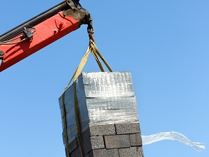 Crane lifting a load of masonry blocks.