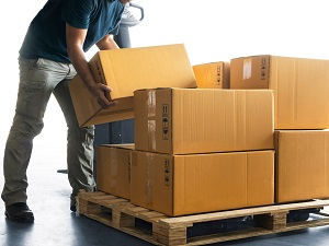 Worker putting boxes onto a pallet.