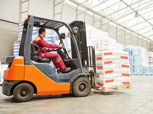 A forklift driver operating a forklift in an unsafe manner because he is not wearing a seatbelt.