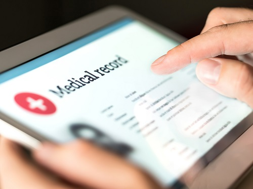 Person viewing medical records on an electronic tablet.