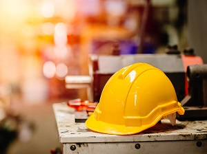A hardhat sitting on an industrial work bench.