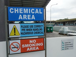"""A sign outside an industrial work space that says """"Chemical Area"""" with a no smoking sign attached."""