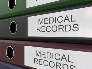 Medical records in large binders that are stacked.