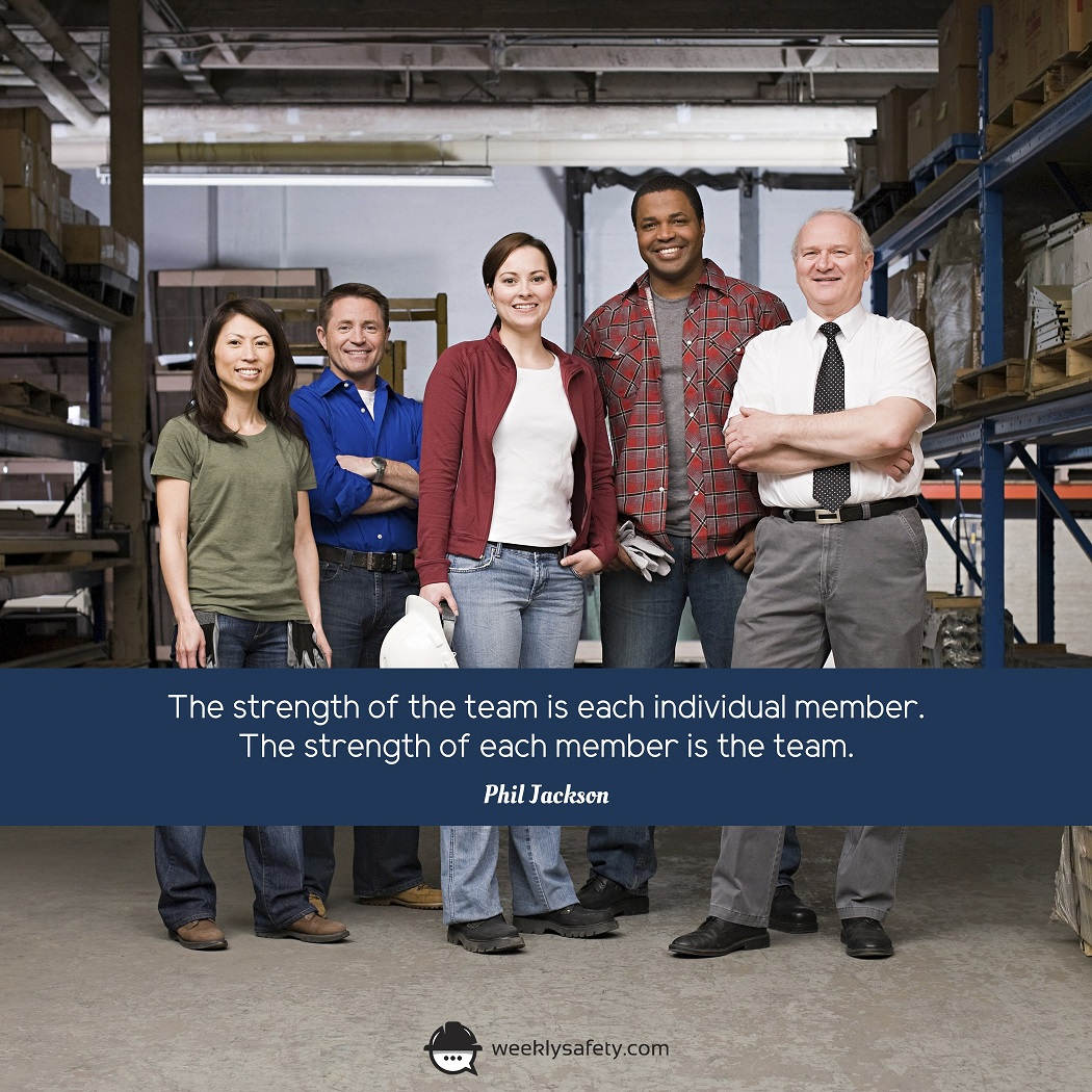 A group of 5 smiling workers standing in a warehouse.