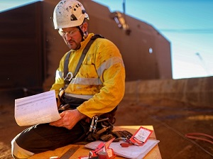 A construction worker on site filling out a job hazard analysis form.