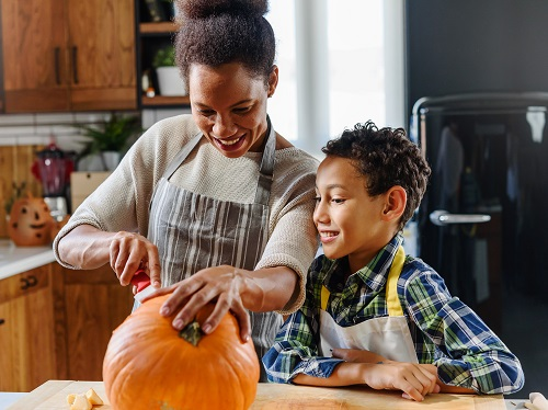 A family safely enjoying the tradition of pumpkin carving together.