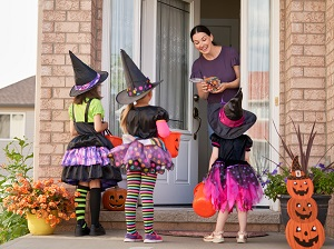 Three young children in costumes who are trick-or-treating.