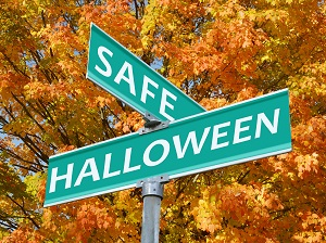 Street signs that say Safe Halloween against a backdrop of fall leaves on trees.