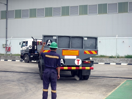 A worker acting as a spotter while guiding the driver of a large truck.
