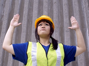 A worker wearing a hard hat and a safety vest using hand signals.