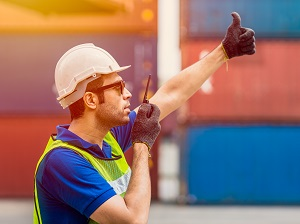 A worker wearing a hard hat and safety vest using hand signals and a walkie-talkie.