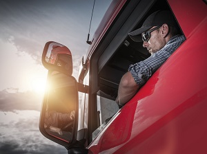 A truck driver looking into the side mirror.