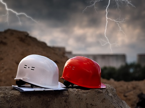 Two hard hats on a construction site with lightning seen in the background.