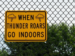 """A chain link fence with a yellow and black sign hanging on it that says, """"When Thunder Roars Go Indoors."""""""