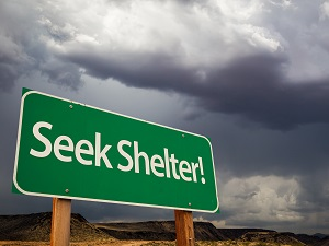 """A green sign against a dark stormy sky that says, """"Seek Shelter!"""""""