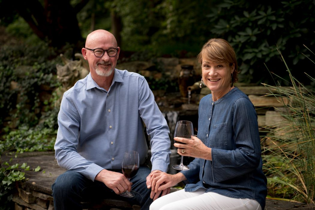 Craig and Lin Boggs drinking wine next to pond