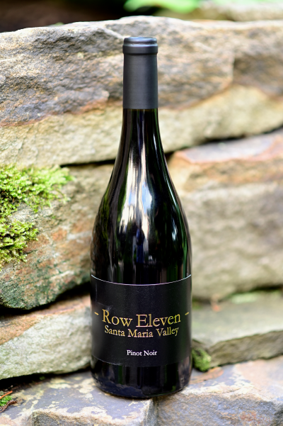 Photo of a bottle of Row Eleven Santa Maria Valley Pinot Noir sitting on stone wall.