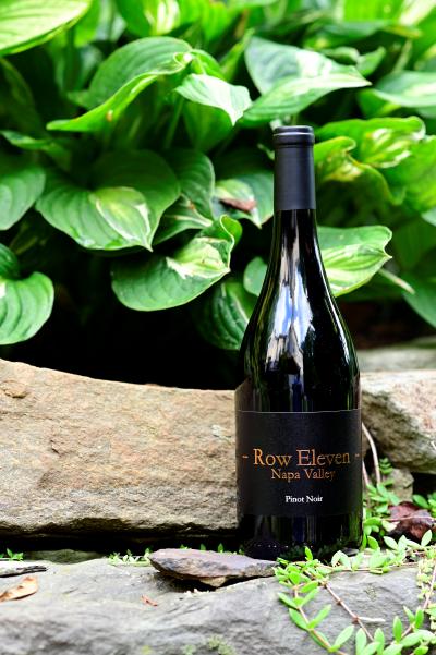 Photo of Row Eleven Napa Valley 2020 bottle next to foliage