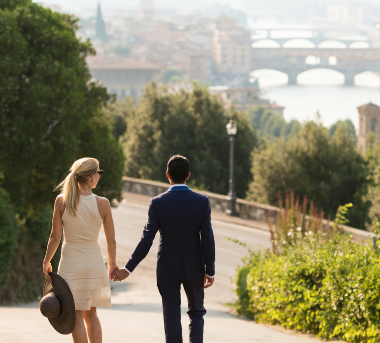 Well-dressed couple strolling through Florence, Italy looking at the Ponte Vecchio