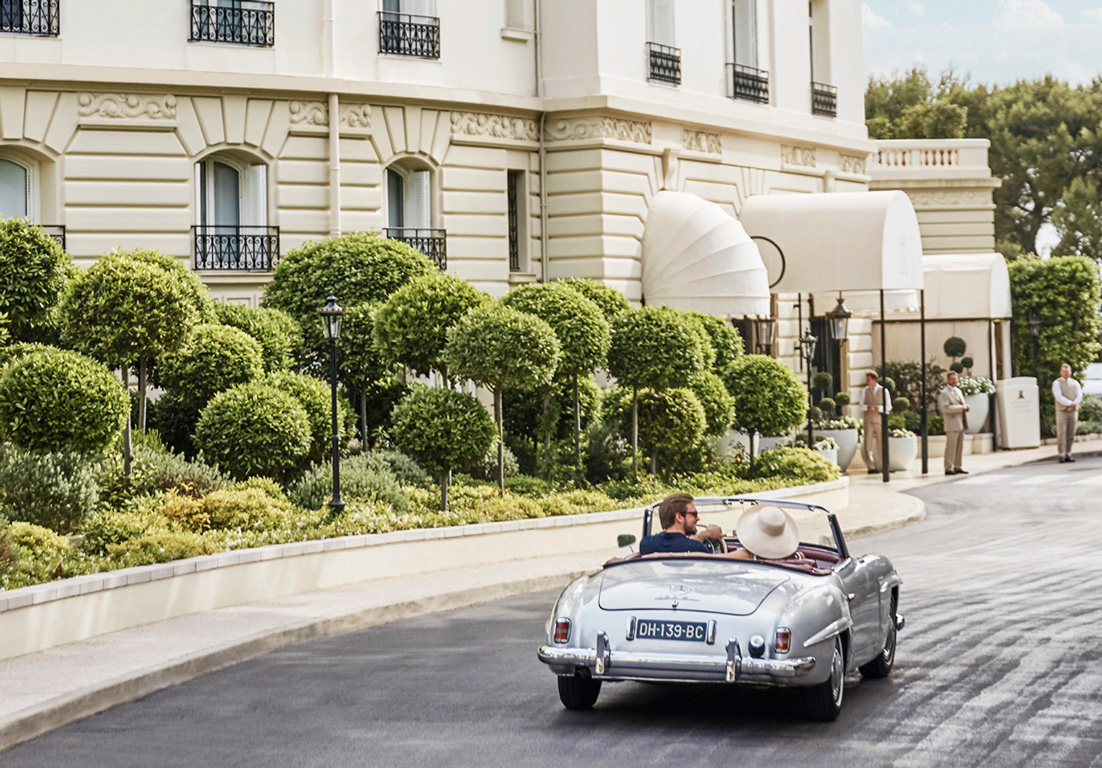 Couple drives the streets of Monte Carlo, Monaco in a retro luxury convertible