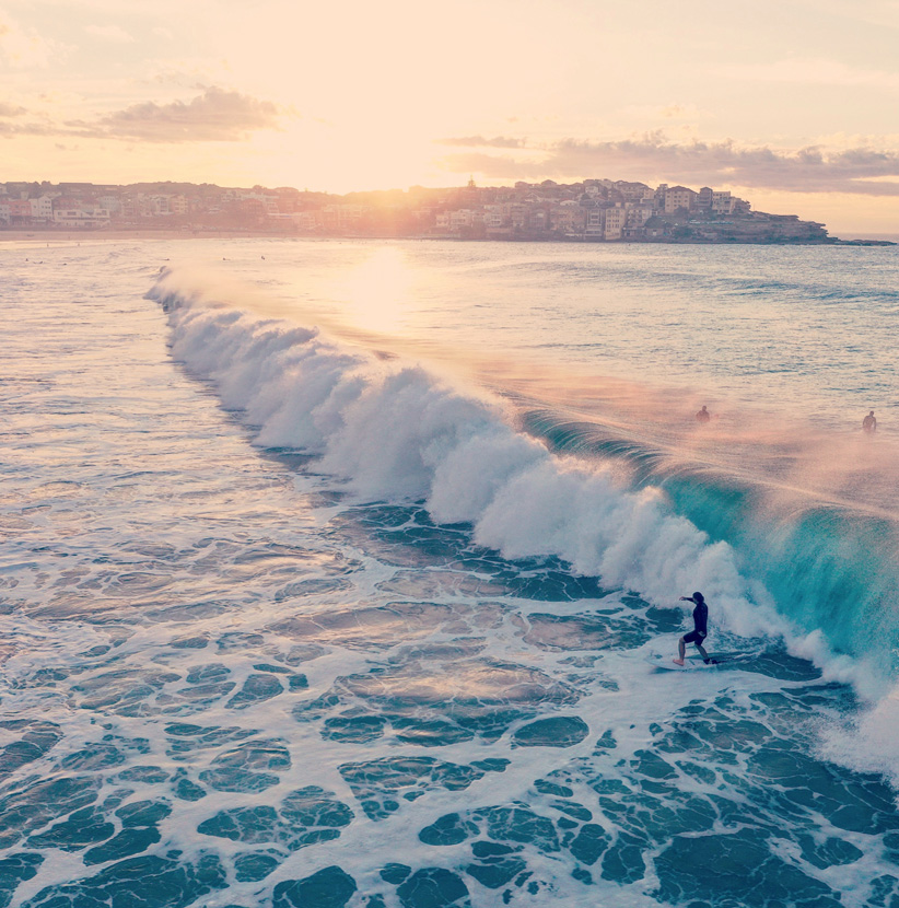 Surfers ride the waves on Bondi Beach, Australia as the sun sets