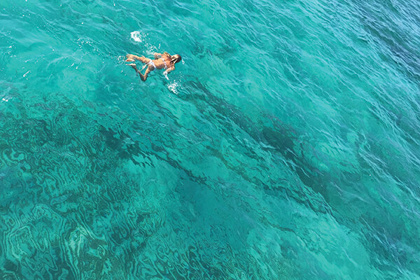 Woman swimming in the turquoise waters of St. Tropez