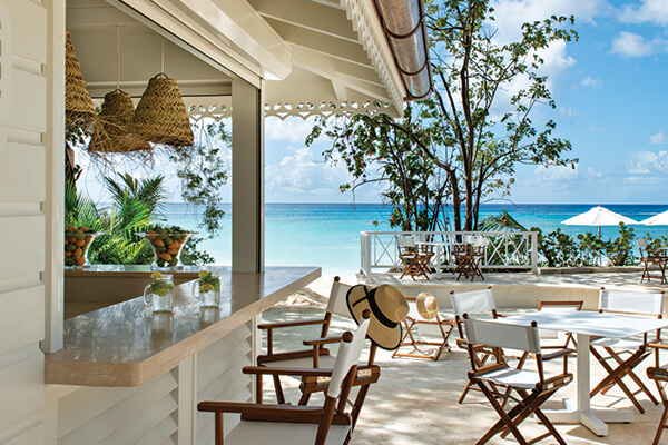 The bar at The Great House, Barbados, overlooks a stunning beach and turquoise waters.