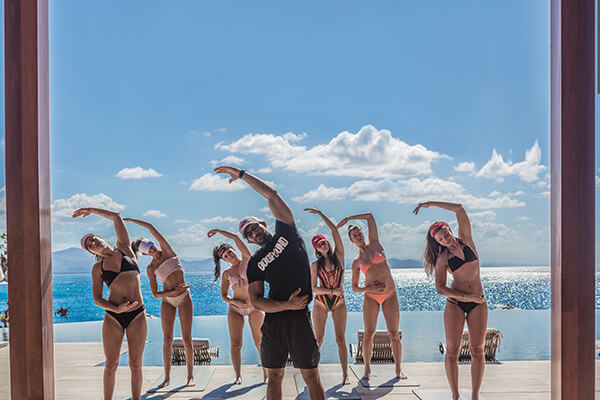A group participate in a beachside morning yoga class at Ani Private Resort, Dominican Republic