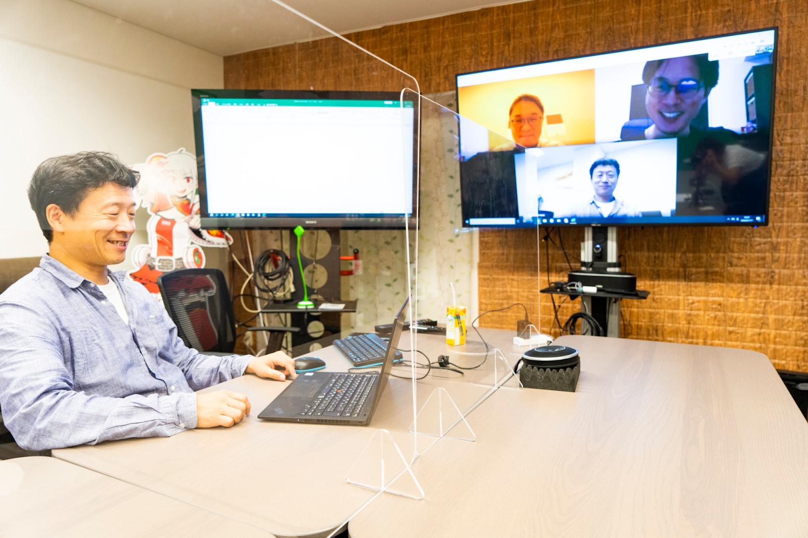 机の上のノートパソコンを見ている男性自動的に生成された説明