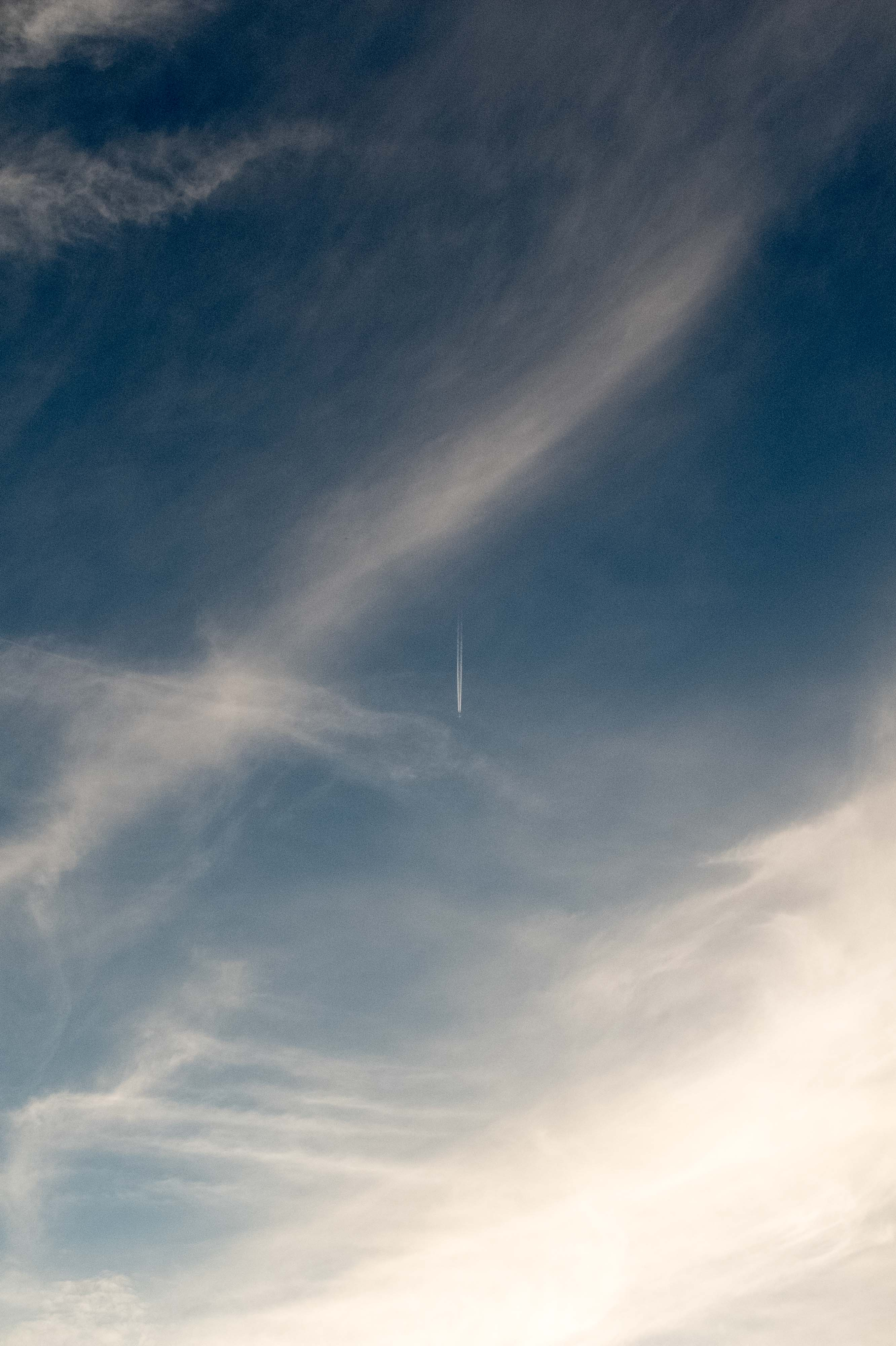Contrail and clouds with blue sky.